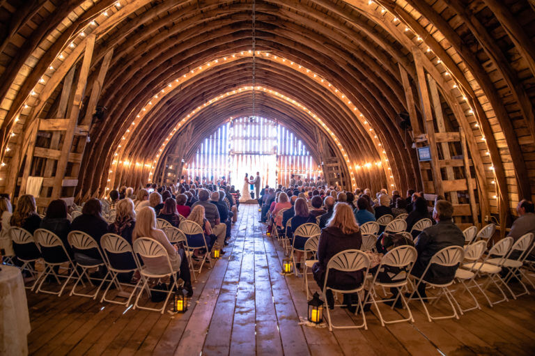Indoor event space — guests witness ceremony under gothic arch barn roof